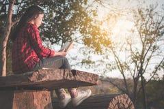 Χαλαρώνοντας ασιατικός τουρίστας στιγμής που διαβάζει ένα βιβλίο στο πάρκο Στοκ Φωτογραφία