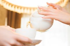 χαλαρώνοντας γυναίκα τσαγιού συμβαλλόμενων μερών ποτών Οι γυναίκες χύνουν το πράσινο τσάι σε ένα άσπρο φλυτζάνι στοκ εικόνα με δικαίωμα ελεύθερης χρήσης