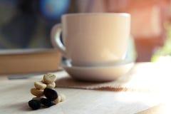 Χαλαρώνοντας στιγμές, φλιτζάνι του καφέ και ένα βιβλίο στον ξύλινο πίνακα στο υπόβαθρο φύσης, χρώμα του εκλεκτής ποιότητας τόνου  στοκ φωτογραφία