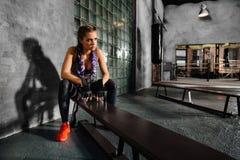 Χαλαρώνοντας συνεδρίαση κοριτσιών ικανότητας στον πάγκο αθλητικών σχολείων μετά από μια σκληρή κατάρτιση εγκιβωτισμού Στοκ Εικόνα