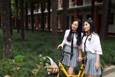 Χαλαρώστε το ασιατικό κινεζικό όμορφο κοστούμι σπουδαστών ένδυσης κοριτσιών στο σχολείο απολαμβάνει το ποδήλατο γύρου ελεύθερου χ στοκ εικόνες