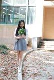 Χαλαρώστε το ασιατικό κινεζικό όμορφο κοστούμι σπουδαστών ένδυσης κοριτσιών στο σχολείο απολαμβάνει το ελεύθερο χρόνο στον κήπο ά στοκ φωτογραφία με δικαίωμα ελεύθερης χρήσης