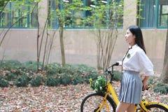 Χαλαρώστε το ασιατικό κινεζικό όμορφο κοστούμι σπουδαστών ένδυσης κοριτσιών στο σχολείο απολαμβάνει το ποδήλατο γύρου ελεύθερου χ στοκ εικόνες με δικαίωμα ελεύθερης χρήσης
