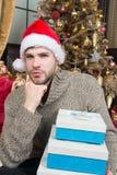 Χαμένος στις σκέψεις Χριστουγέννων Ευτυχές άτομο με τα κιβώτια δώρων Χριστουγέννων Ο τύπος γιορτάζει τα Χριστούγεννα στο σπίτι άτ στοκ εικόνα