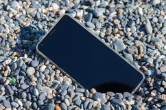 Χαμένο κινητό τηλέφωνο στην παραλία μεταξύ των μικρών χαλικιών θάλασσας στοκ εικόνες