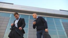 Χαμηλή άποψη γωνίας δύο ευτυχών νέων επιχειρηματιών με τον αστείο χορό χαρτοφυλάκων περπατώντας μετά από την επιτυχή επιχειρησιακ απόθεμα βίντεο