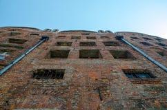 Χαμηλή άποψη γωνίας του εγκαταλειμμένου σπιτιού τούβλου με τα σπασμένα παράθυρα με στοκ εικόνες με δικαίωμα ελεύθερης χρήσης