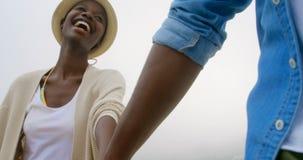 Χαμηλή άποψη γωνίας του ζεύγους αφροαμερικάνων που περπατά με χέρι-χέρι στην παραλία 4k απόθεμα βίντεο