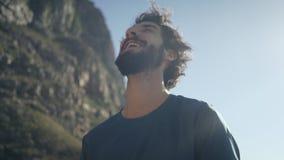 Χαμηλή άποψη γωνίας του χαμογελώντας οδοιπόρου που κοιτάζει ενάντια στον ουρανό φιλμ μικρού μήκους