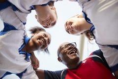Χαμηλή άποψη γωνίας των θηλυκών ποδοσφαιριστών και του προπονητή γυμνασίου που διοργανώνουν τη συζήτηση ομάδας στοκ εικόνες