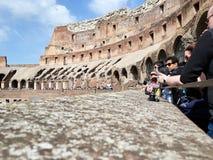 Χαμηλή άποψη γωνίας των τουριστών μέσα του Colosseum κατά τη διάρκεια της ημέρας με τις κάμερες στοκ εικόνες