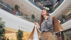 Χαμηλή γωνία που πυροβολείται μιας ευτυχούς γυναίκας με τις τσάντες αγορών που εξετάζει γύρω τη λεωφόρο απόθεμα βίντεο