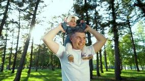 Χαμηλή γωνία που πυροβολείται του ευτυχούς πατέρα που κρατά την κόρη μικρών παιδιών του στους ώμους έξω φιλμ μικρού μήκους