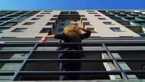 Χαμηλή γωνία που πυροβολείται του νέου ξανθού χορού γυναικών κοντά στα κιγκλιδώματα μετάλλων στην οδό πόλεων απόθεμα βίντεο