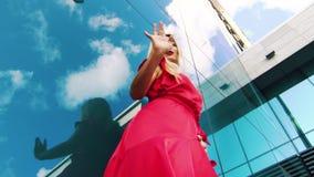 Χαμηλή γωνία που πυροβολείται του νέου χορού γυναικών κοντά στην απεικόνιση της επιφάνειας του ουρανοξύστη απόθεμα βίντεο