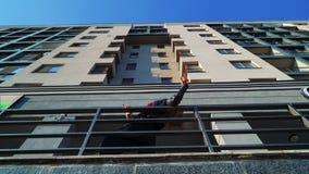 Χαμηλή γωνία που πυροβολείται του ξανθού θηλυκού που χορεύει κοντά στα κιγκλιδώματα μετάλλων του σύγχρονου κτηρίου απόθεμα βίντεο