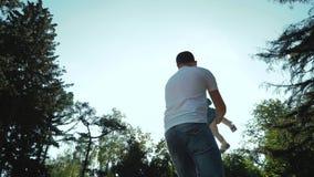 Χαμηλή γωνία που πυροβολείται του παιχνιδιού πατέρων με την κόρη μικρών παιδιών στο θερινό πάρκο φιλμ μικρού μήκους