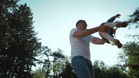 Χαμηλή γωνία που πυροβολείται του πατέρα που έχει τη διασκέδαση με την κόρη μικρών παιδιών στο θερινό κήπο απόθεμα βίντεο