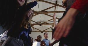 Χαμηλή γωνία πυροβοληθείσα, ευτυχής ομάδα επιχειρηματιών που κάνει το χορό διασκέδασης μαζί στο σύγχρονο multiethnic κόμμα εορτασ φιλμ μικρού μήκους