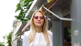 Χαμηλή γωνία της αρκετά ξανθής γυναίκας στα γυαλιά ηλίου που περπατά κάτω από την οδό απόθεμα βίντεο