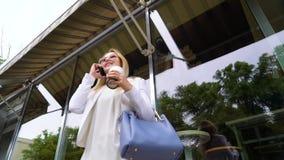 Χαμηλή γωνία της μοντέρνης διαπραγμάτευσης επιχειρησιακών γυναικών με το συνεργάτη στο smartphone φιλμ μικρού μήκους