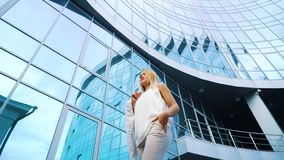 Χαμηλή γωνία της πανέμορφης ξανθής γυναίκας που απεικονίζει πλησίον την επιφάνεια του ουρανοξύστη απόθεμα βίντεο