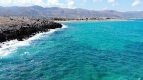Χαμηλή εναέρια μύγα κατά μήκος της δύσκολης παραλίας και της μπλε θάλασσας, Κρήτη απόθεμα βίντεο