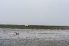 Χαμηλή παλίρροια με τη βάρκα που βάζει στην πλευρά Στοκ Φωτογραφία