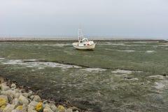 Χαμηλή παλίρροια με τη βάρκα που βάζει στην πλευρά Στοκ Εικόνες