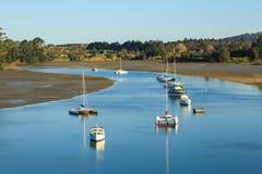 Χαμηλή παλίρροια σε ένα λιμάνι, με τις βάρκες που επιπλέουν σε ένα κανάλι στοκ φωτογραφία