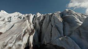 Χαμηλή πτήση κινηματογραφήσεων σε πρώτο πλάνο πέρα από τις βαθιές ρωγμές ενός ορεινού σερνμένος παγετώνα 4K Παγετώνας που κονιοπο φιλμ μικρού μήκους