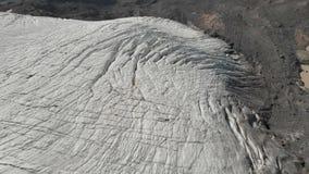 Χαμηλή πτήση κινηματογραφήσεων σε πρώτο πλάνο πέρα από τις βαθιές ρωγμές ενός ορεινού σερνμένος παγετώνα 4K Παγετώνας που κονιοπο απόθεμα βίντεο