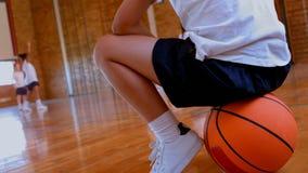 Χαμηλή συνεδρίαση μαθητριών τμημάτων καυκάσια στην καλαθοσφαίριση στο γήπεδο μπάσκετ στο σχολείο φιλμ μικρού μήκους