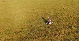 Χαμηλή τροχιακή πτήση γύρω από το άτομο στην πράσινη χλόη με το μαξιλάρι σημειωματάριων στον κίτρινο αγροτικό τομέα φιλμ μικρού μήκους