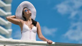 Χαμηλή όμορφη γυναίκα γωνίας στα γυαλιά ηλίου και στάση χαμόγελου καπέλων χαλαρώνοντας στο μέσο πυροβολισμό μπαλκονιών απόθεμα βίντεο
