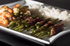 Χαμηλός εξαερωτήρας - πράσινα φασόλια που τυλίγονται στα μικτά λαχανικά και το ρύζι μπέϊκον woth στο άσπρο πιάτο Στοκ Φωτογραφία