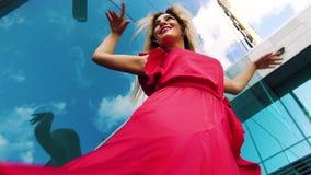 Χαμηλός πυροβολισμός γωνίας της αισθησιακής γυναίκας στο κόκκινο φόρεμα που χορεύει ενάντια στην επιφάνεια καθρεφτών φιλμ μικρού μήκους