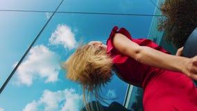 Χαμηλός πυροβολισμός γωνίας της προκλητικής γυναίκας στο κόκκινο φόρεμα που χορεύει στο αστικό περιβάλλον απόθεμα βίντεο