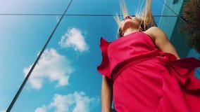 Χαμηλός πυροβολισμός γωνίας της προκλητικής κυρίας στο κόκκινο φόρεμα που χορεύει υπαίθρια ενάντια στην επιφάνεια καθρεφτών φιλμ μικρού μήκους