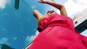Χαμηλός πυροβολισμός γωνίας της προκλητικής ξανθής γυναίκας στο κόκκινο φόρεμα που χορεύει ενάντια στον ουρανοξύστη απόθεμα βίντεο