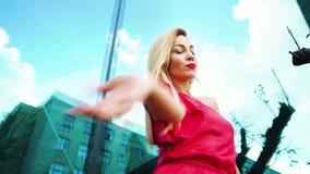 Χαμηλός πυροβολισμός γωνίας της χορεύοντας ξανθής γυναίκας στο κόκκινο φόρεμα κοντά στην πρόσοψη καθρεφτών απόθεμα βίντεο