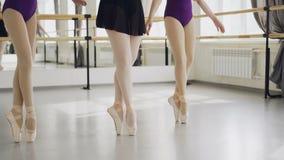 Χαμηλός πυροβολισμός των θηλυκών ποδιών στα παπούτσια μπαλέτου που κάνουν plie έπειτα να χορεψει tiptoe στο πάτωμα του ελαφριού σ φιλμ μικρού μήκους