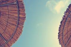 Χαμηλή άποψη γωνίας σχετικά με το άχυρο δύο parasols με το μπλε ουρανό στη μέση  εξασθενισμένο, αναδρομικό ύφος Στοκ Φωτογραφία