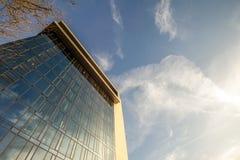 Χαμηλή άποψη γωνίας της αντανάκλασης του μπλε ουρανού στον τοίχο γυαλιού σύγχρονου Στοκ Εικόνες