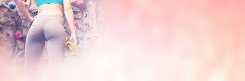 Χαμηλή άποψη γωνίας της εξέτασης γυναικών επάνω τον τοίχο αναρρίχησης βράχου Στοκ Εικόνες