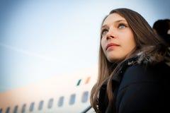 Χαμηλή άποψη γωνίας του πορτρέτου γυναικών μπροστά από το αεροπλάνο ενάντια στον ουρανό Στοκ εικόνες με δικαίωμα ελεύθερης χρήσης
