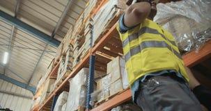 Χαμηλή γωνία που πυροβολείται ενός εργαζομένου διοικητικών μεριμνών σε μια μεγάλη αποθήκη εμπορευμάτων