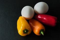 Χαμηλός εξαερωτήρας - δύο άσπρα αυγά με τρεις ζωηρόχρωμες μίνι πάπρικες σε ένα σκοτεινό υπόβαθρο πλακών στοκ φωτογραφίες