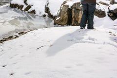 Χαμηλότερο μέρος του θηλυκού ταξιδιώτη που στέκεται στο χιόνι Στοκ εικόνα με δικαίωμα ελεύθερης χρήσης