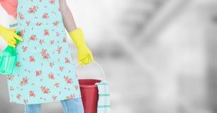 Χαμηλότερο σώμα γυναικών στην ποδιά με τον κάδο στο μουτζουρωμένο γκρίζο κλίμα Στοκ φωτογραφία με δικαίωμα ελεύθερης χρήσης